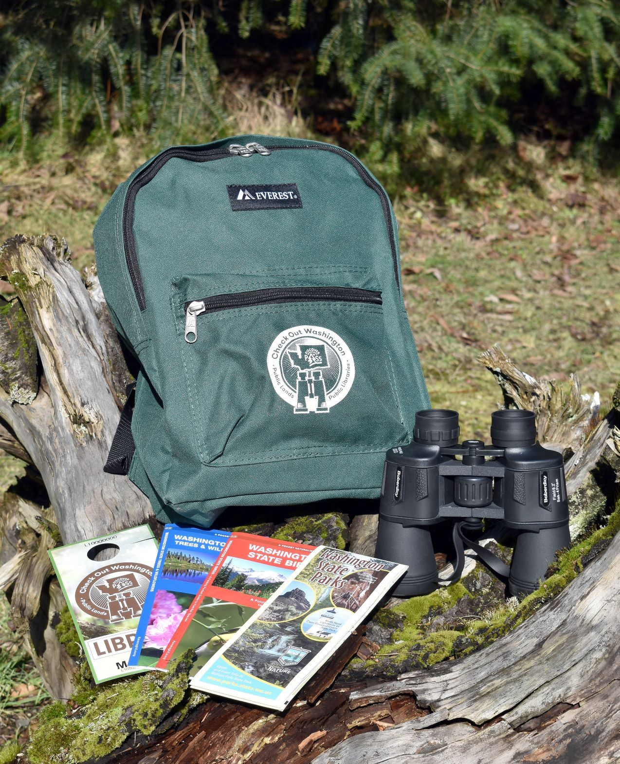 Check Out WA Backpack on a log with discover pass, brochures, binoculars